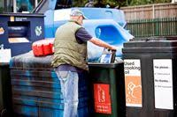 Man recycling waste at a Household Waste Recycling Centre
